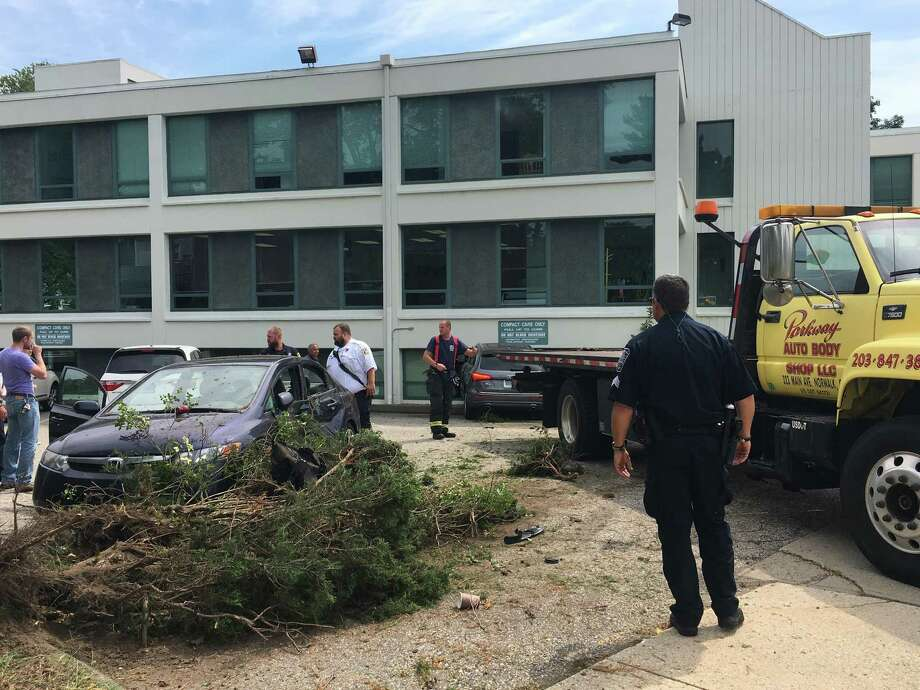 A car struck a building at 83 East Avenue on Monday afternoon on Aug. 21, 2017. The accident that also involved another vehicle in the parking brought first responders to the scene around 1 p.m. Police on the scene are trying to determine what caused the vehicle to hit the building. Photo: Leslie Lake /Hearst Connecticut Media