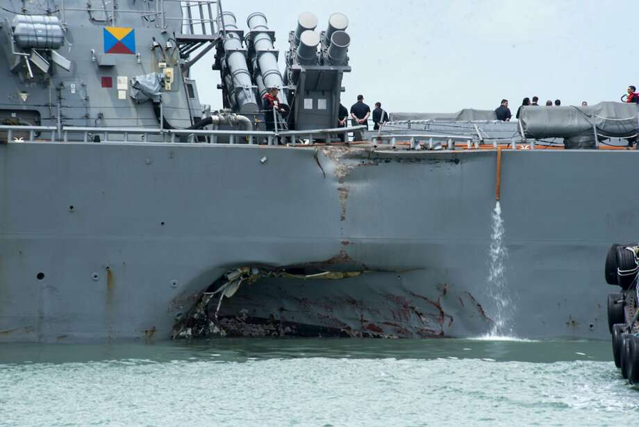 Damage to the port side is visible on the John S. McCain as the destroyer steers toward a naval base in Singapore after a collision with a merchant vessel. Ten sailors are missing. Photo: Mass Communication Specialist 2nd Class Joshua Fulton, Associated Press