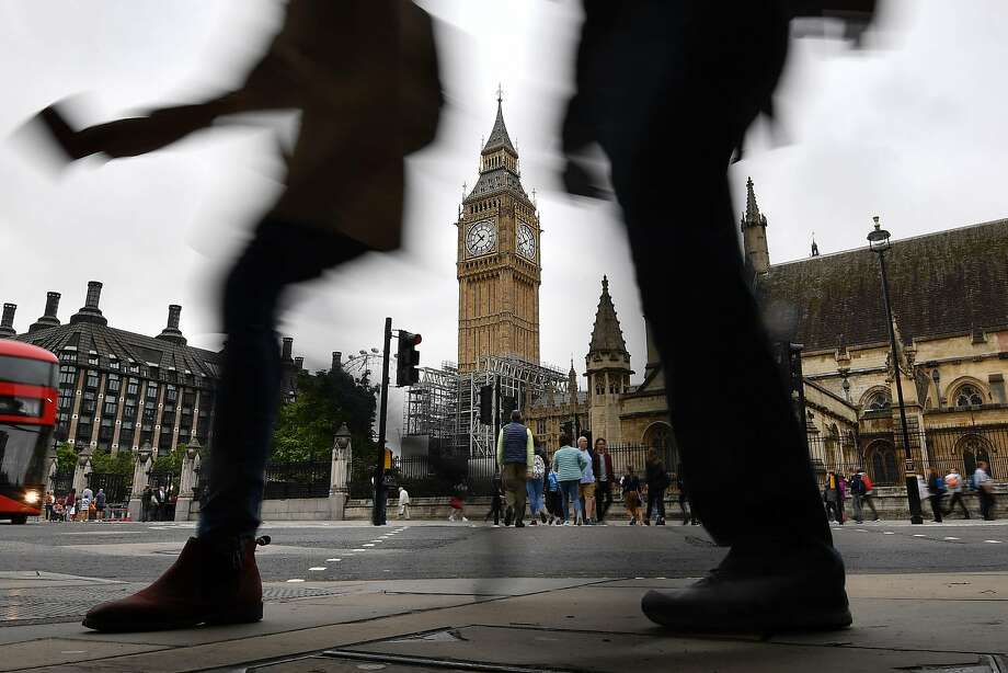 Pedestrians in London's Parliament Square pass Elizabeth Tower and Big Ben. The bell is being stilled to allow workers to do repairs on the clock and clock tower without being deafened. Photo: BEN STANSALL, AFP/Getty Images