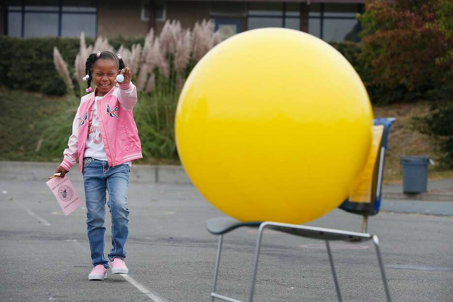 Deja, 6, holds a ball up to compare it with another while learning about distance, perspective and obscuration during the eclipse at Mira Vista School on Monday, August 21, 2017 in Richmond, Calif. Photo: Lea Suzuki, The Chronicle