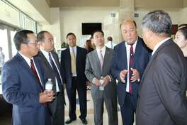 Yuhai Zhao, chairman of the Yihai Group, (second from right) talks to a group of Chinese delegates during an Aug. 16 visit to the city of Cleveland. Zhao's company is developing the Grand Oaks Reserve and Cleveland West Industrial Park.