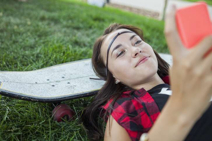Teenage girl with cell phone laying on skateboard Details Credit: Hero Images