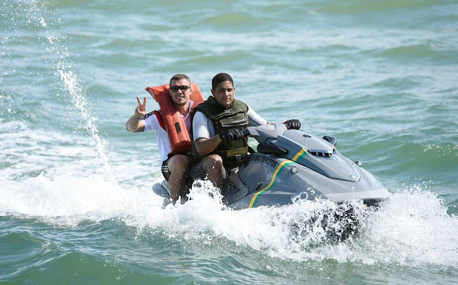German national soccer player Lukas Podolski poses on a jet ski in Santo Andre near Porto Seguro, Brazil, Tuesday, June 10, 2014. This photo was used to illustrate a Breitbart article on illegal immigrants using personal watercraft. Photo: Markus Gilliar/AP
