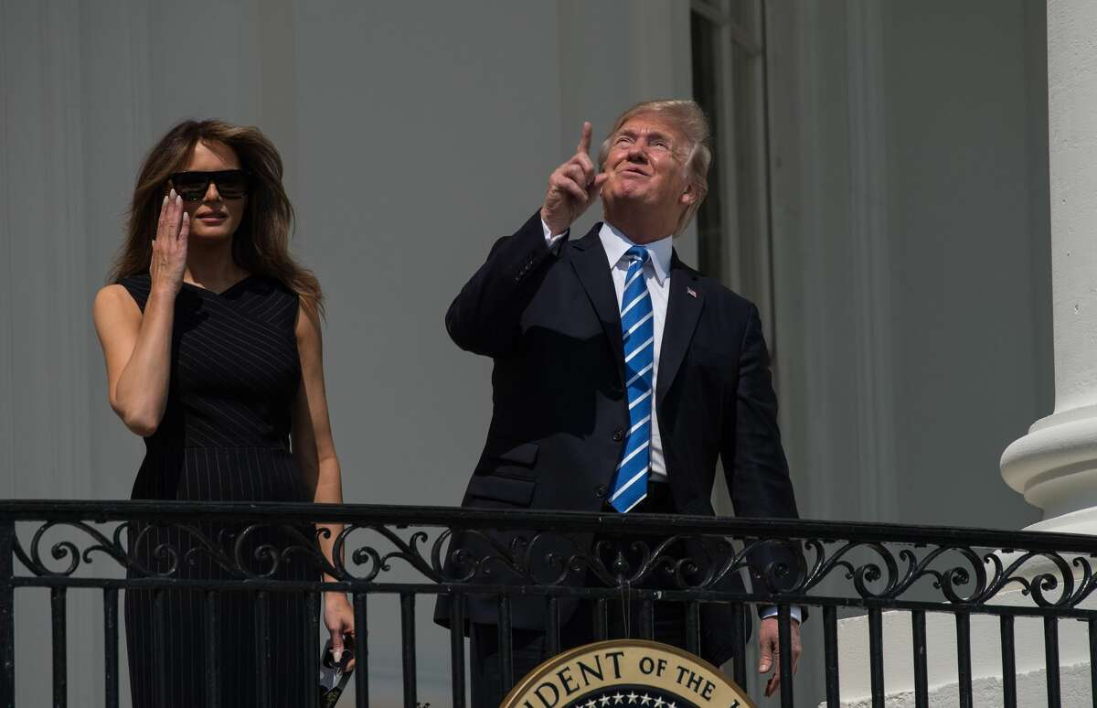 US President Donald Trump looks up a the partial solar eclipse with First Lady Melania Trump from the balcony of the White House in Washington, DC, on August 21, 2017. The Great American Eclipse completed its journey across the United States Monday, with the path of totality stretching coast-to-coast for the first time in nearly a century.