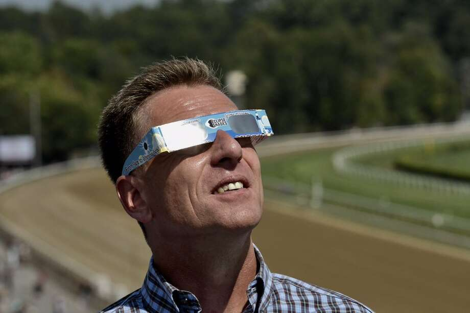 Former jockey Richard Migliore, a winner of horse racing's Eclipse Award, watches the partial solar eclipse on Monday, Aug. 21, 2017, atop Saratoga Race Course in Saratoga Springs. (Skip Dickstein/Times Union) Photo: Skip Dickstein/Times Union