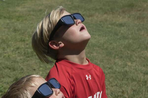 Logan and Hudson Hammontree use solar glasses to see the eclipse as they and others from around the Permian Basin crowd the grounds at Museum of the Southwest 8/21/17 afternoon to view the solar eclipse.  Tim Fischer/Reporter-Telegram