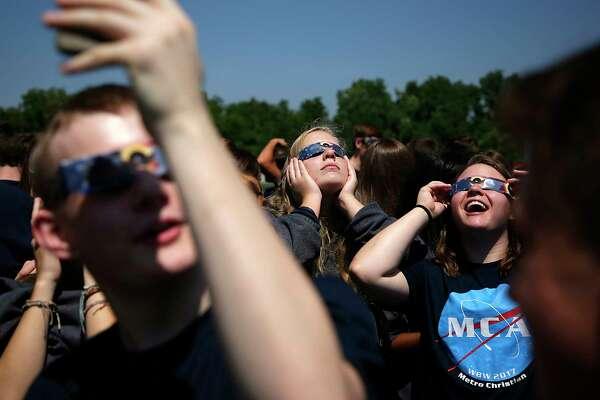 Juniors Annie Blankenship, center, and Hallie Burn watch the solar eclipse at Metro Christian Academy, Monday, Aug. 21, 2017. (Mike Simons/Tulsa World via AP)