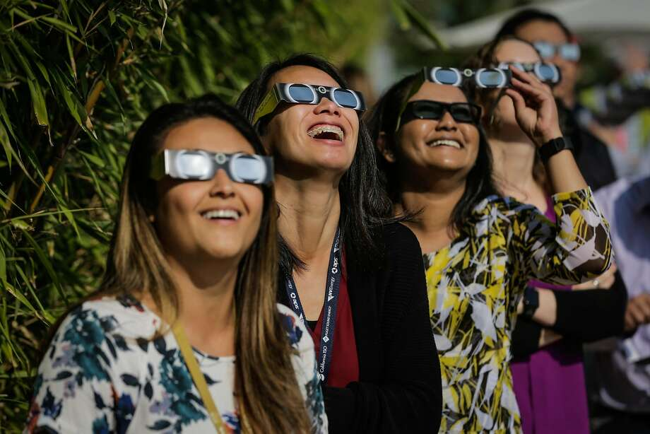 Kathryn Wills (left), Karen Voong and Vashna Manisha watch the solar eclipse near the headquarters of the California Independent System Operator in Folsom. Photo: Gabrielle Lurie, The Chronicle