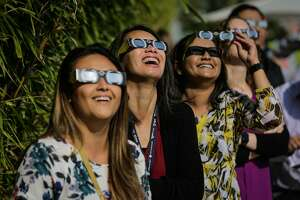 (l-r) Kathryn Wills, Karen Voong and Vashna Manisha watch the solar eclipse at the California Independent System Operator in Folsom, Calif., on Monday, Aug. 21, 2017.