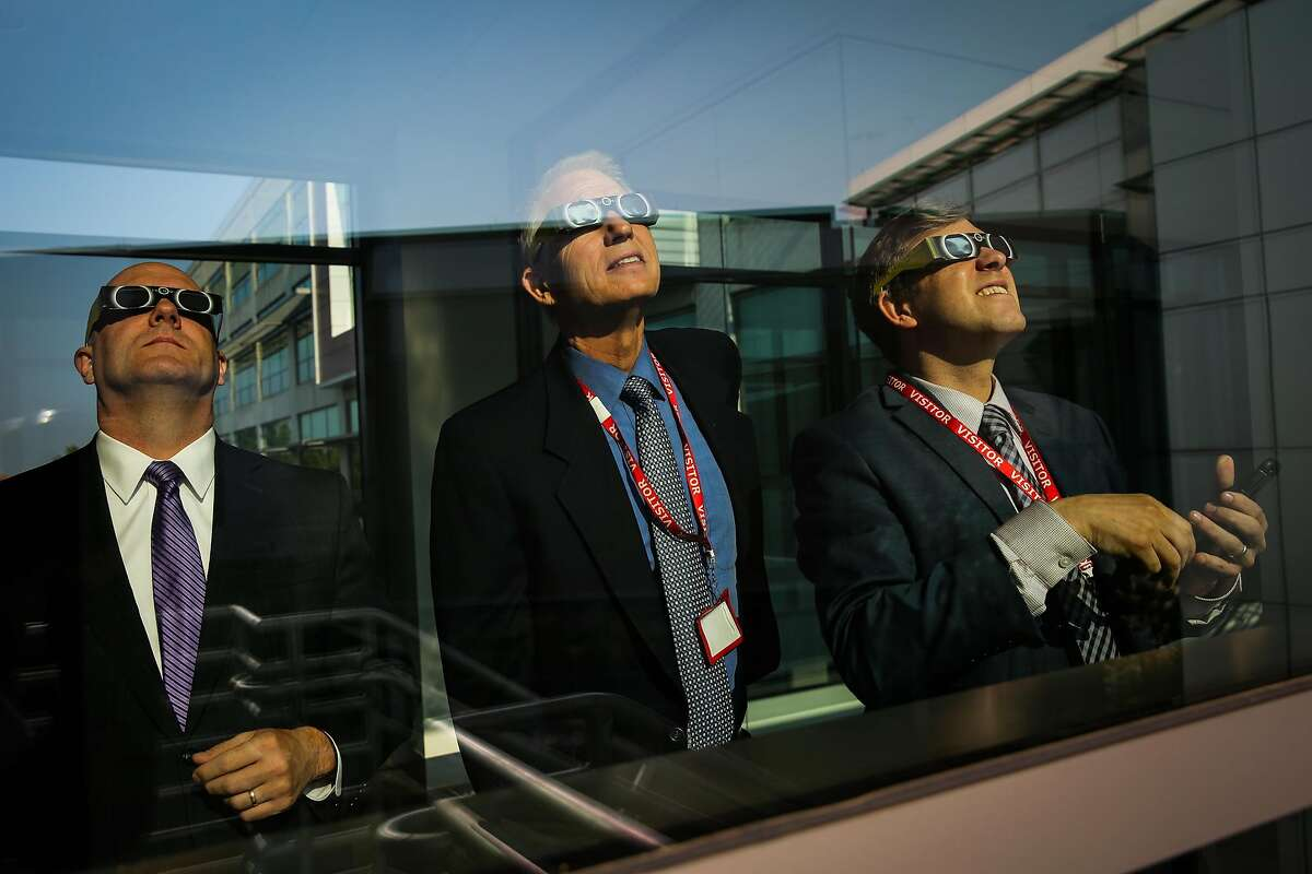 (l-r) Steve Berberich, Albert Lundeen and Kevin Barker look at the solar eclipse as it begins at the California Independent System Operator in Folsom, Calif., on Monday, Aug. 21, 2017.