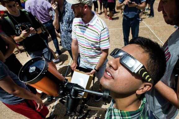 Akash Gupta, a Rice University senior, looks skyward to view the partial eclipse of the sun at Rice University on Monday, Aug. 21, 2017, in Houston.