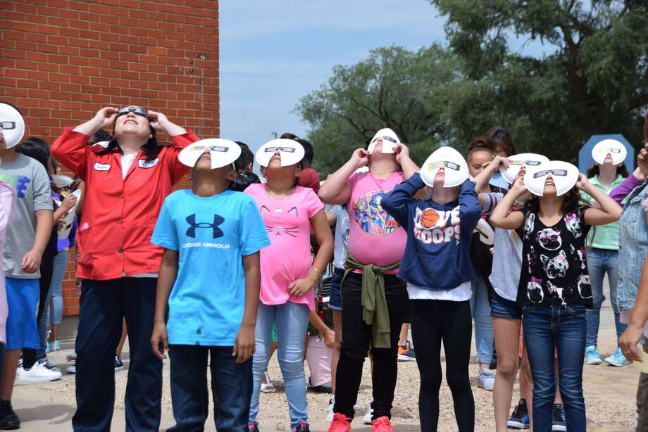 Fifth grade students at Thunderbird Elementary view the solar eclipse through eclipse glasses enhanced with paper plate shields for extra viewing protection.