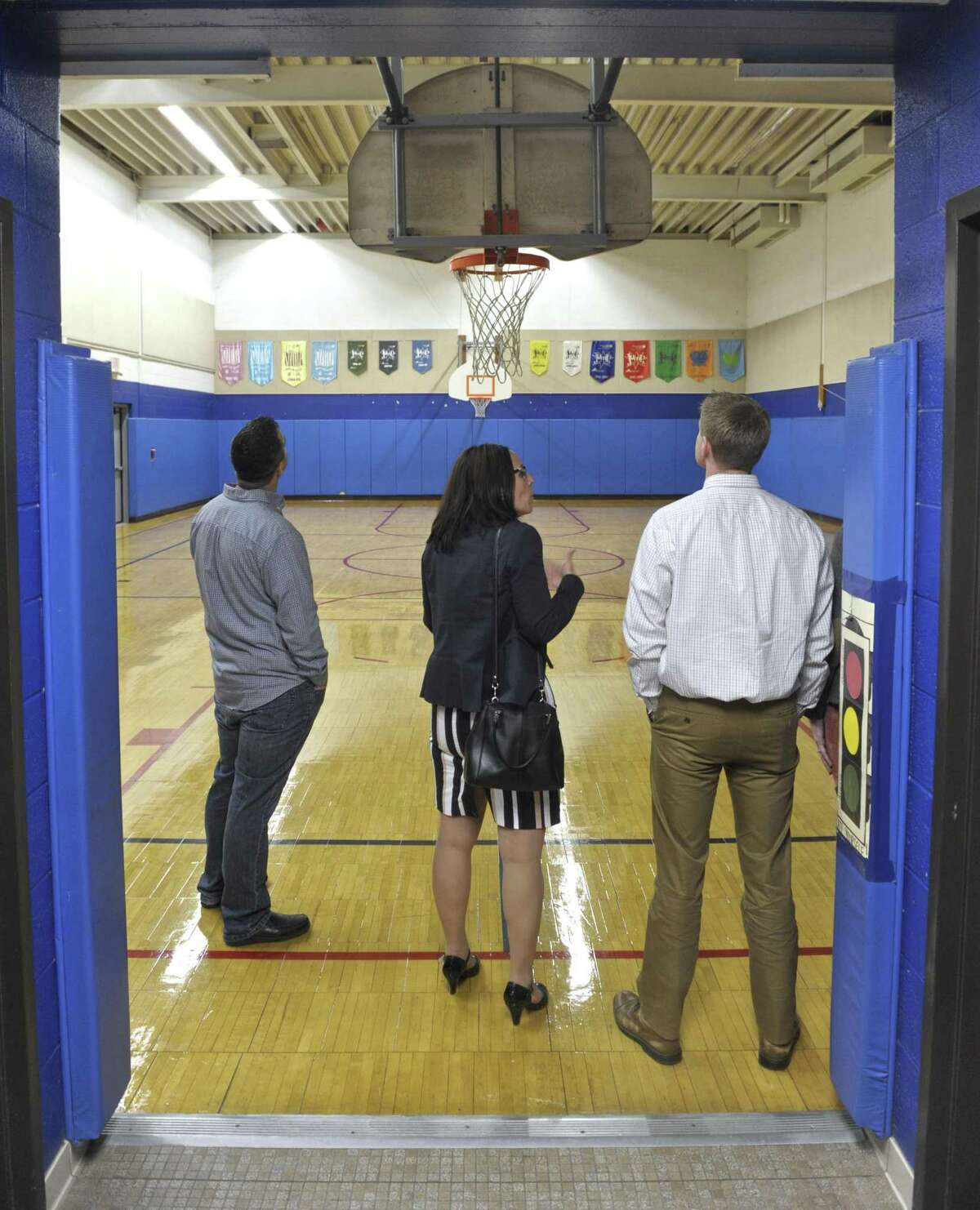 Kevin McCloskey, left and Jim Sveda, right, listen to Bethel Superintendent of Schools Christine Carver during a tour of Rockwell School. Wednesday, October 5, 2016, in Bethel, Conn. The Sveda and McCluskey have children in the school.