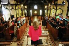 Angel Choir director Pamela Kuhn leads a rehearsal inside St. Andrews Church in Stamford on Sunday.