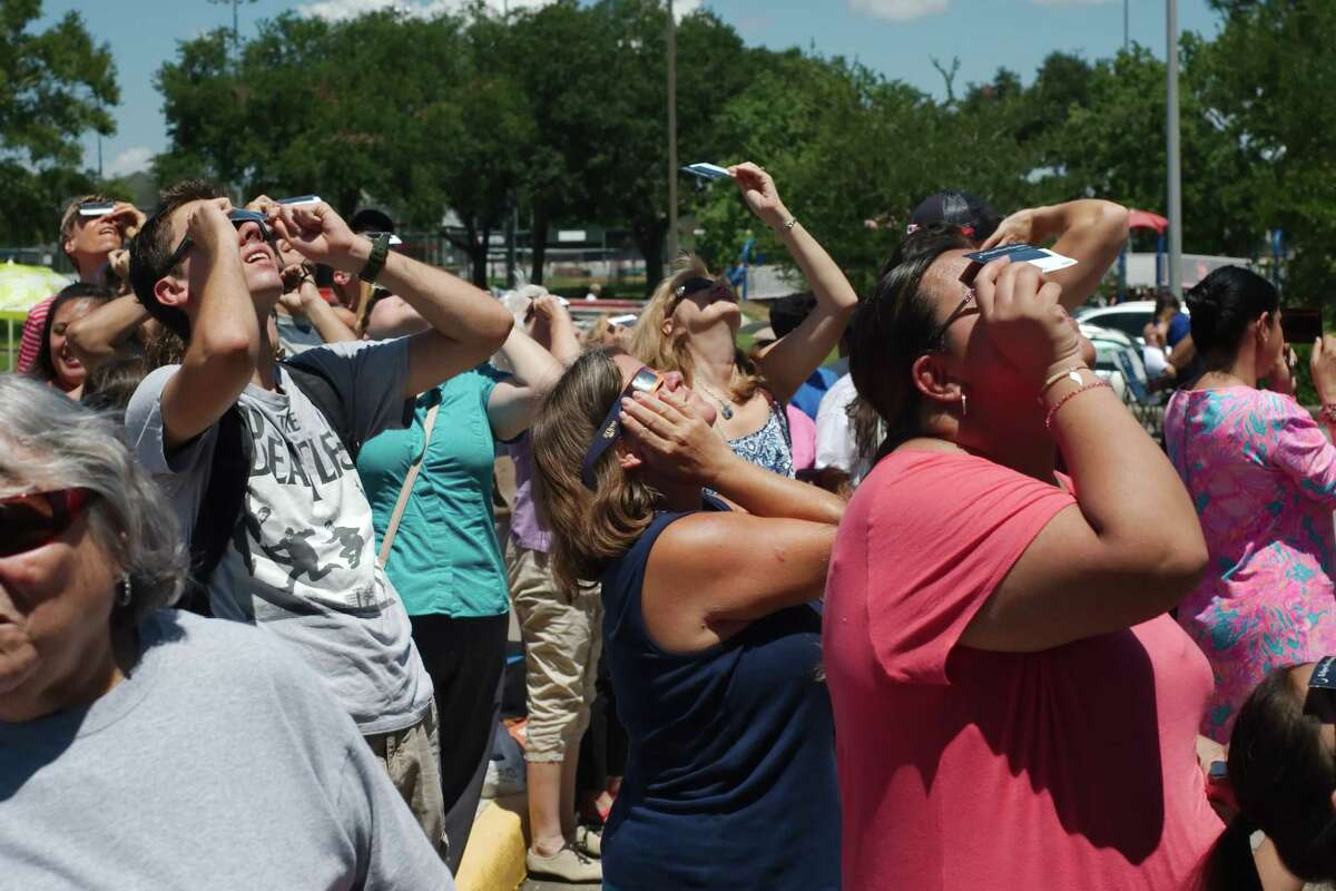 Drew Snell, Cathy Jett and Monse Salinas look through protective glasses as they view the solar eclipse at Harris County Freeman Library Monday, Aug. 21.