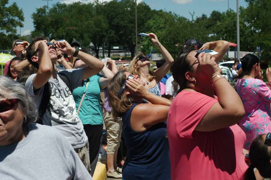 Drew Snell, Cathy Jett and Monse Salinas look through protective glasses as they view the solar eclipse at Harris County Freeman Library Monday, Aug. 21. Photo: Kirk Sides / © 2017 Kirk Sides / Houston Chronicle