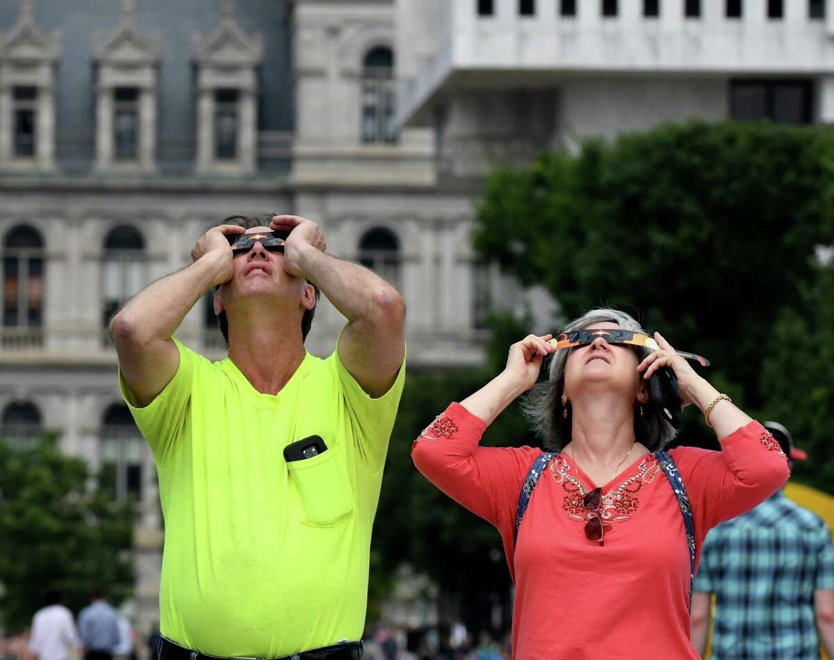 Mark Harmer Cohoes, left, and Cheryl Bellus Troy, right, view a solar eclipse on the Empire State Plaza on Monday, Aug. 21, 2017, in Albany, N.Y. (Will Waldron/Times Union)