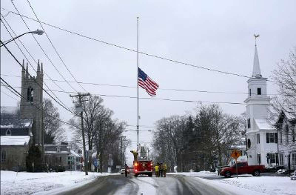 On the first anniversary of the Sandy Hook massacre, firefighters lower the town's flag on Main Street to half-staff in honor of the victims, Saturday, Dec. 14, 2013, in Newtown, Conn.