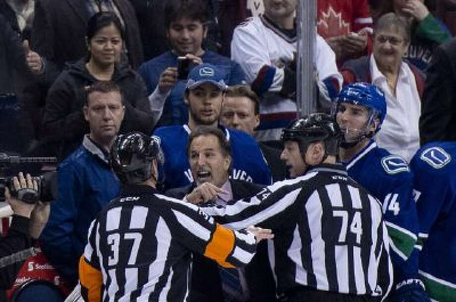 Referees get in the way of Vancouver Canucks head coach John Tortorella.