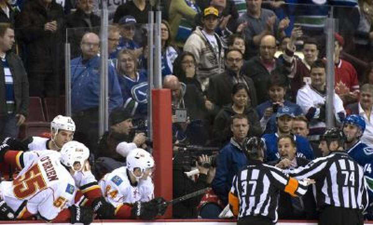 Referees get in the way of Vancouver Canucks head coach John Tortorella as he screams at the Calgary Flames bench during first period of a Saturday game.