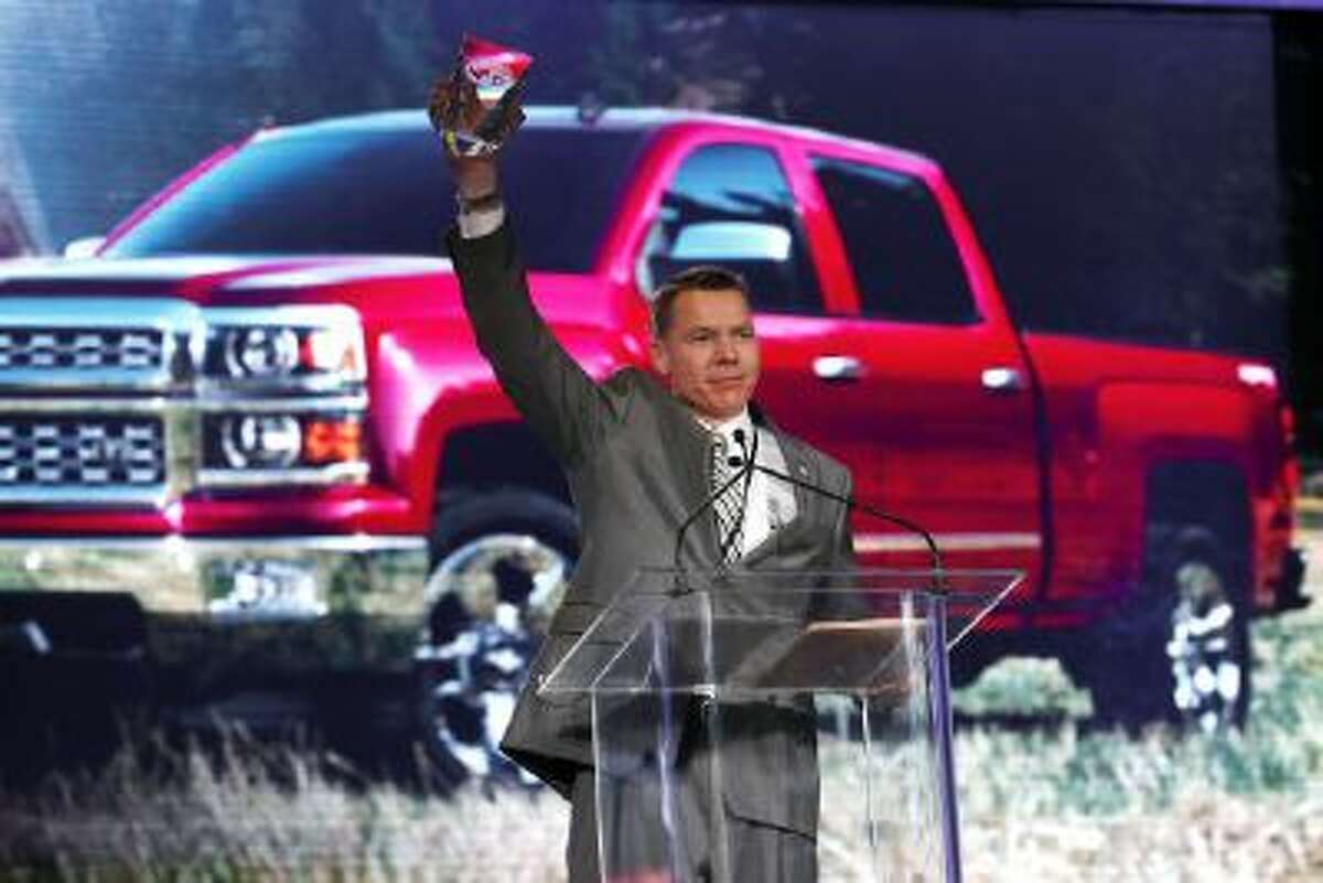 General Motors executive chief engineer Jeffrey Luke holds up the North American Truck of the Year award after the Chevrolet Silverado won at the North American International Auto Show in Detroit, Monday, Jan. 13, 2014.