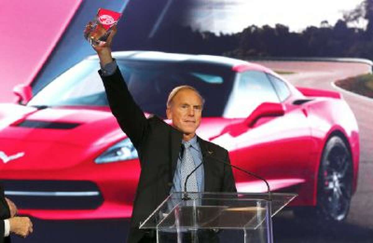 Chevrolet Corvette Stingray chief engineer Tadge Juechter holds up the North American Car of the Year award at the North American International Auto Show in Detroit, Monday, Jan. 13, 2014.