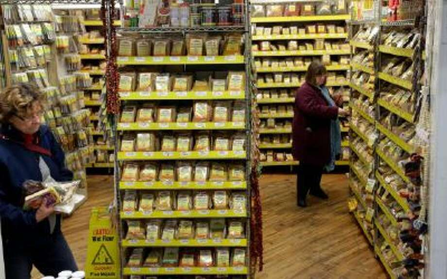 In this Nov. 21, 2013 photo, two women shop wall after wall of bags of dried herbs and spices, nearly all of them imported, processed and packaged by Kalustyan's, at Kalustyan's Indian/Middle Eastern spice and specialty food shop in New York.