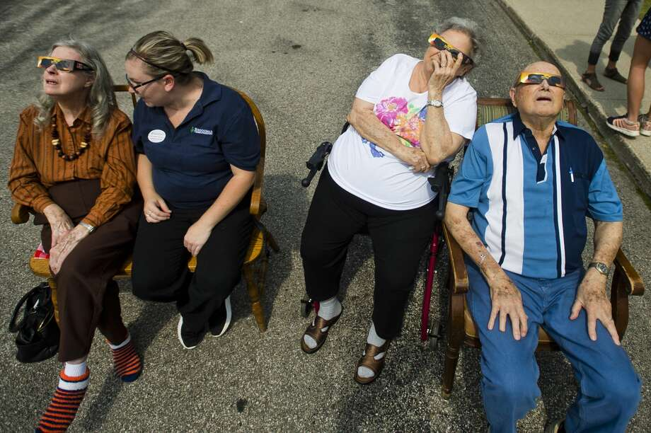 Residents and staff of Brookdale Assisted Living watch the solar eclipse through special glasses on Monday, August 21, 2017 in Midland. Photo: (Katy Kildee/kkildee@mdn.net)