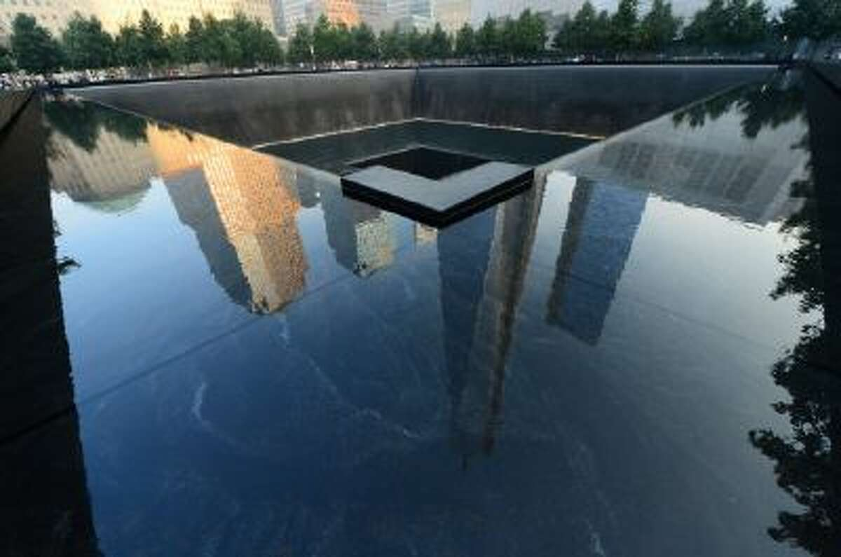 This Sept. 11, 2013 file photo shows One World Trade Center, center, is reflected on the polished wall of the September 11 Memorial on the 12th anniversary of the terrorist attacks on the World Trade Center in New York.