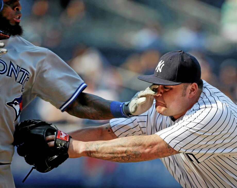 New York Yankees relief pitcher Joba Chamberlain, right, gets a hand in his eye while tagging out Toronto Blue Jays' Jose Reyes during the ninth inning in the first baseball game of a doubleheader at Yankee Stadium Tuesday, Aug. 20, 2013, in New York. (AP Photo/Seth Wenig) Photo: AP / AP