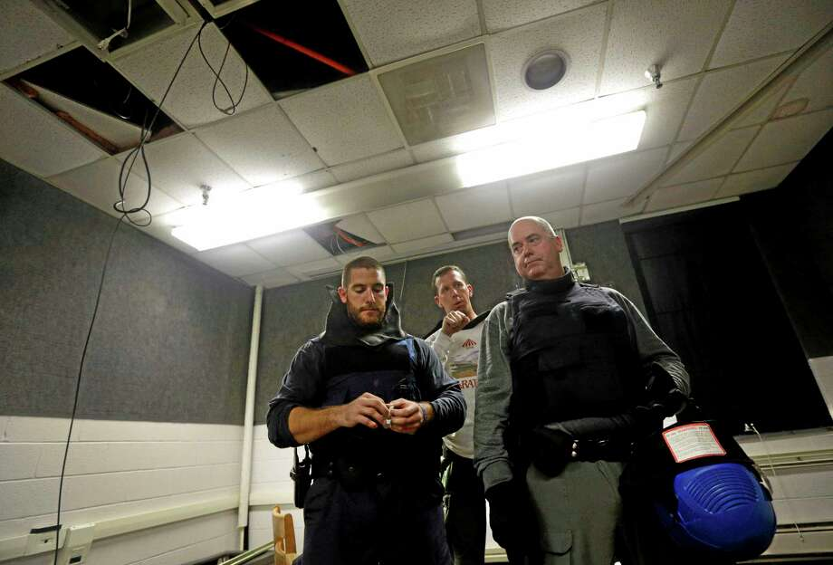 In this Tuesday, Aug. 13, 2013 picture, Maryland State Police instructor Mark McGwire, center, prepares Officer Nick Amendolagine, left, of the Salisbury, Md., Police Department, and Lt. Conrad Meil of the Centreville, Md., Police Department, for an active shooter drill in a college classroom in Salisbury, Md., as part of an FBI program that teaches local law enforcement best practices for responding to mass shootings. The goal is to promote a standardized strategy as multiple local police departments -- invariably the first officers at any scene -- respond to the same shooting. (AP Photo/Patrick Semansky) Photo: AP / AP