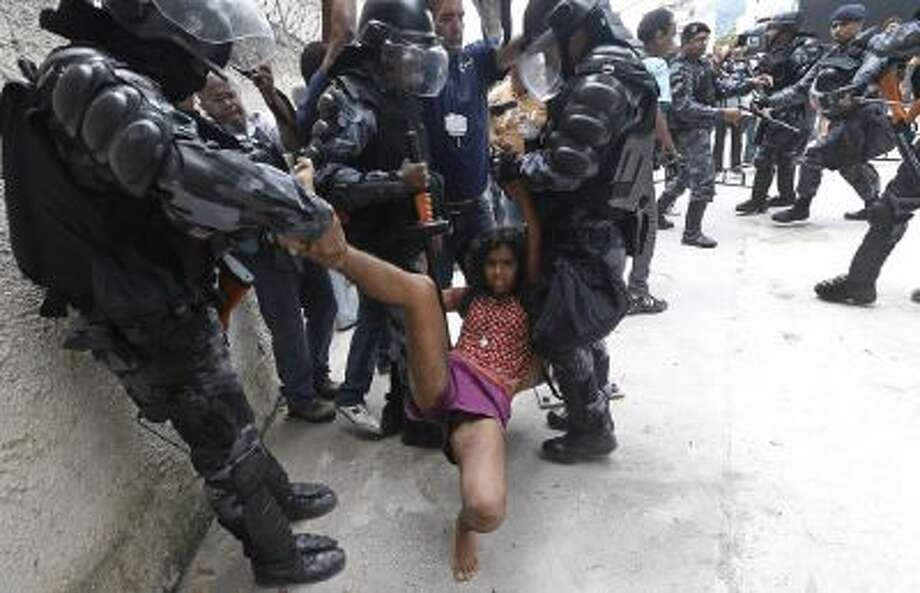 A supporter of indigenous people is carried away by police officers during a protest at the old Indian Museum next to the Maracana stadium in Rio de Janeiro, Brazil, Monday, Dec. 16, 2013.