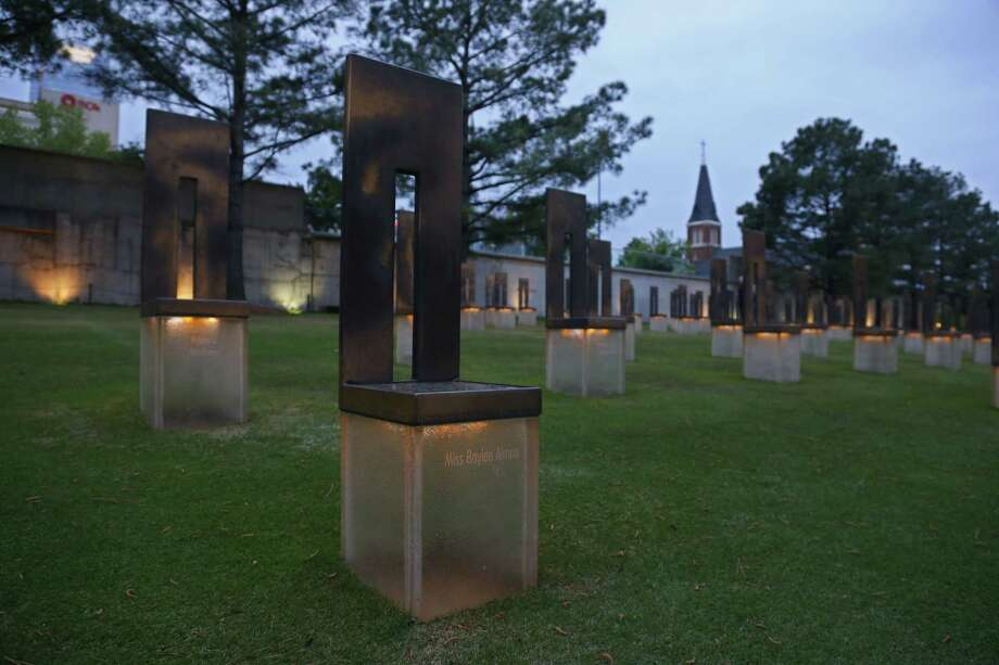 The chair dedicated to bombing victim Baylee Almon is pictured in the Field of Empty Chairs at the Oklahoma City National Memorial at dusk in Oklahoma City, Tuesday, April 14, 2015. Sunday will be the 20th anniversary of the Oklahoma City bombing. The  Alfred P. Murrah Federal Building,was located where the Field of Empty Chairs is now. Almon was the baby pictured in the iconic Pulitzer Prize-winning photo of the bombing. (AP Photo/Sue Ogrocki) Photo: AP / AP