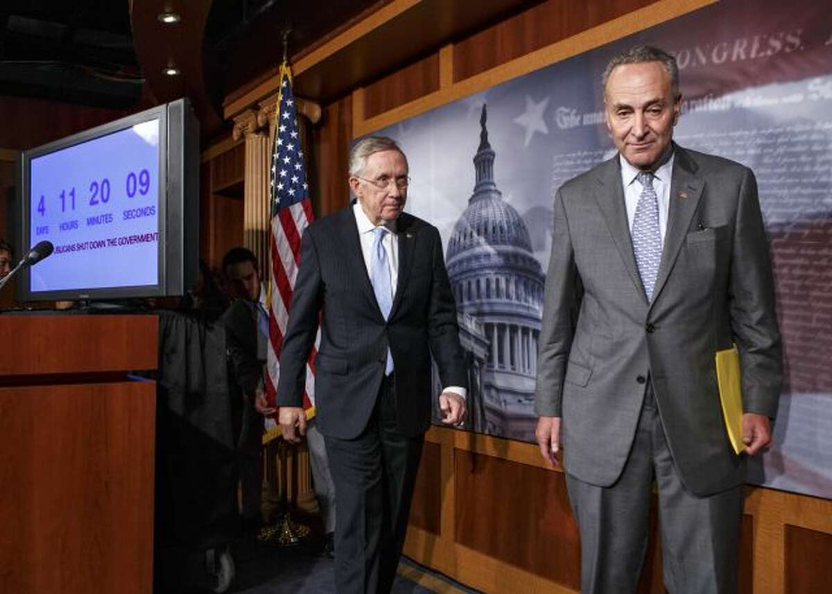 Senate Majority Leader Harry Reid of Nev., left, follows Sen. Charles Schumer, D-N.Y., right, the Democratic Policy Committee chairman, after a news conference on Capitol Hill in Washington, Thursday, Sept. 26, 2013, after blaming conservative Republicans for holding up a stopgap spending bill to keep the government running. Senate passage of the spending bill - stripped of the