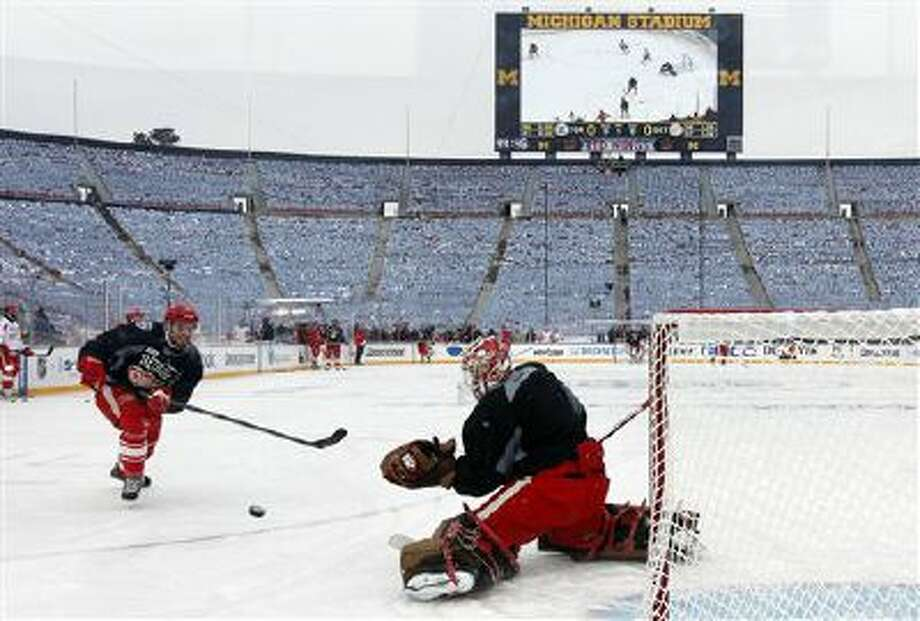 Detroit Red Wings defenseman Brian Lashoff (23) shoots on goalie Jimmy Howard (35) during practice on the outdoor rink for the NHL Winter Classic hockey game against the Toronto Maple Leafs at Michigan Stadium in Ann Arbor, Mich., Tuesday, Dec. 31, 2013. The game is scheduled for New Year's Day. (AP Photo/Paul Sancya) Photo: AP / AP