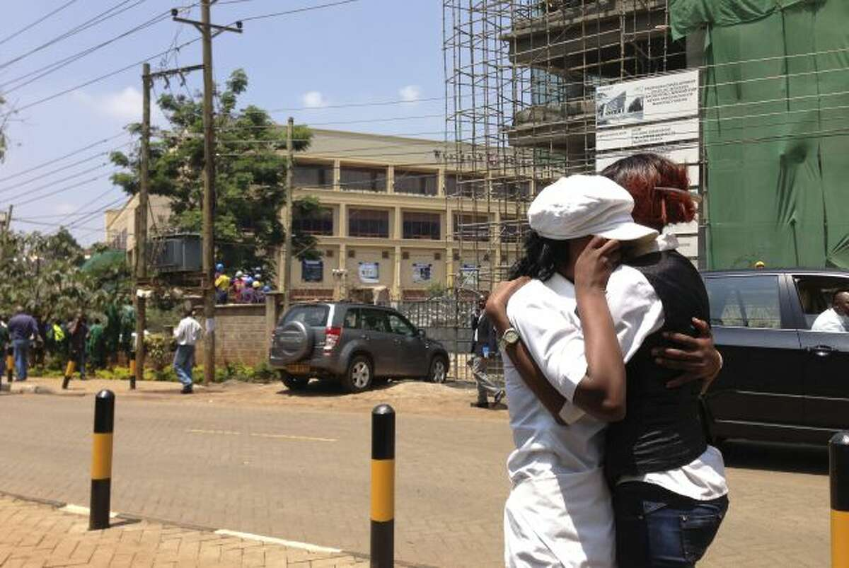 Two women hug outside an upscale shopping mall, seen background left , in Nairobi, Kenya Saturday Sept. 21 2013, after shooting erupted when armed men attempted to rob a store. Bursts of gunfire were heard from outside the mall Saturday, where cars were left abandoned. Witnesses say a half dozen grenades also went off along with lobbies of gunfire that started at midday. Police say they are engaging the attackers. (AP Photo/ Jason Straziuso)