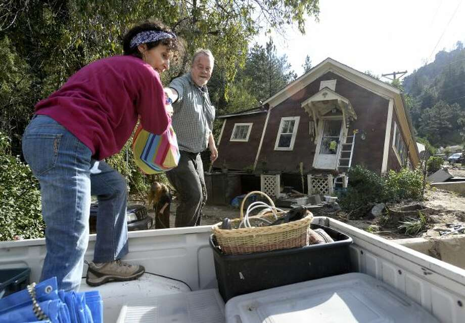 Shireen Malik, left, and Bruce Orr help salvage belongings out of the home of Kathleen McLellan in Salina, Colo., on Thursday, Sept. 19, 2013, in Boulder County. Residents displaced by last week's flooding in the Colorado returned Thursday to salvage what they could from their homes. (AP Photo/The Daily Camera, Jeremy Papasso) NO SALES Photo: AP / Daily Camera