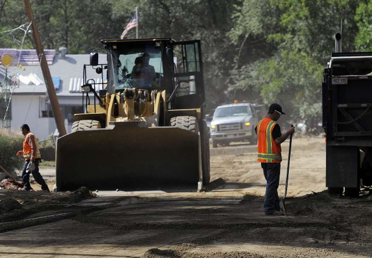 A construction crew works on repairing Park St. in Lyons, Colo., on Thursday, Sept. 19, 2013. Local governments are starting to clear debris and repair infrastructure after last week's flooding. (AP Photo/Chris Schneider)