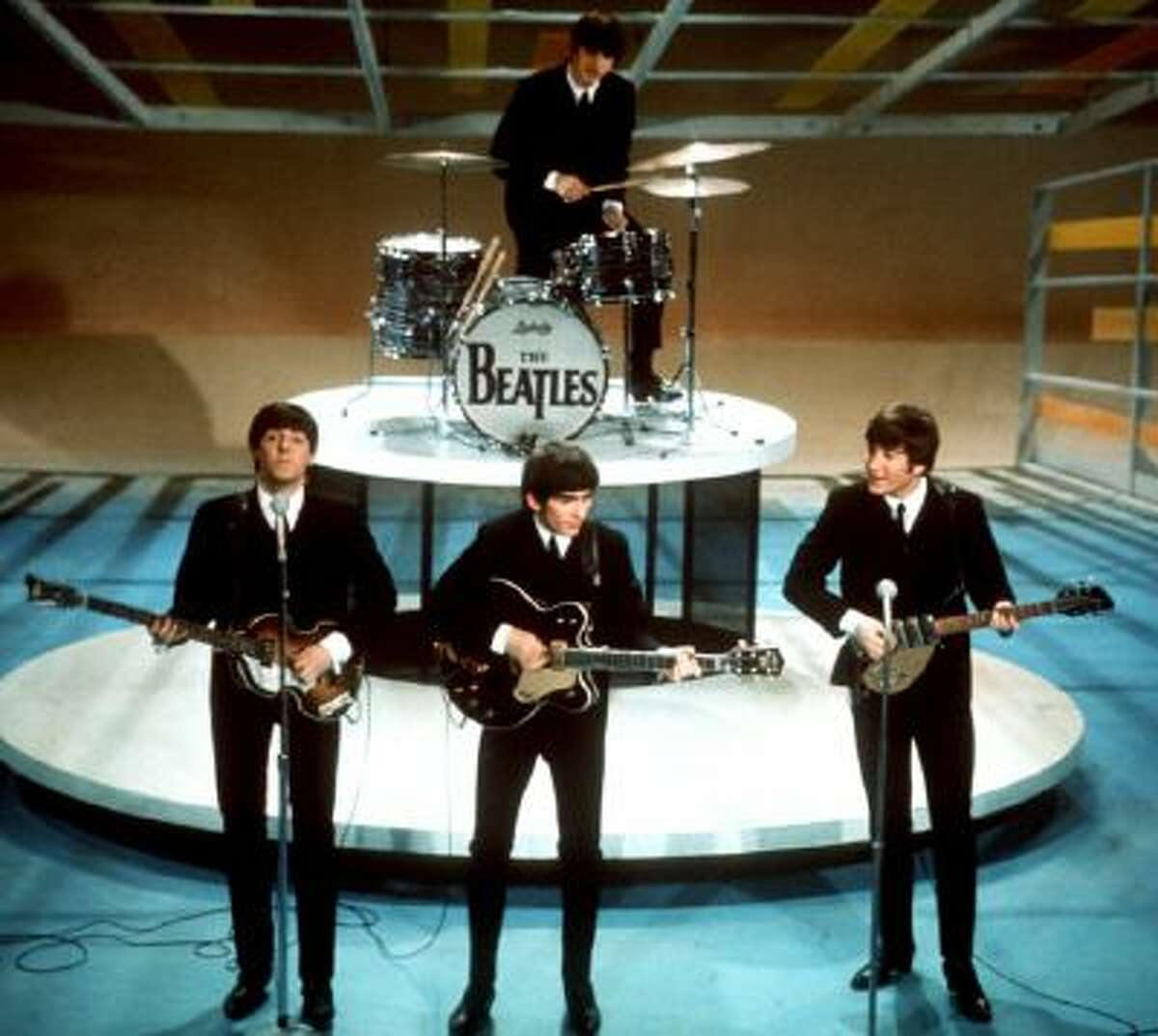 """In this Feb. 9, 1964 photo, The Beatles, from left, Paul McCartney, George Harrison, Ringo Starr on drums, and John Lennon perform on the CBS """"Ed Sullivan Show"""" in New York."""