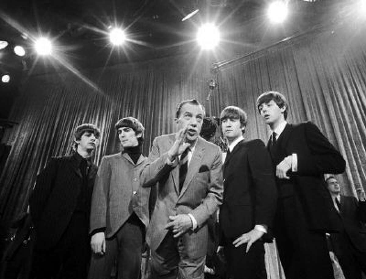 """In this Feb. 9, 1964 photo, Ed Sullivan, center, stands with The Beatles, from left, Ringo Starr, George Harrison, John Lennon, and Paul McCartney, during a rehearsal for the British group's first American appearance, on the """"Ed Sullivan Show,"""" in New York."""