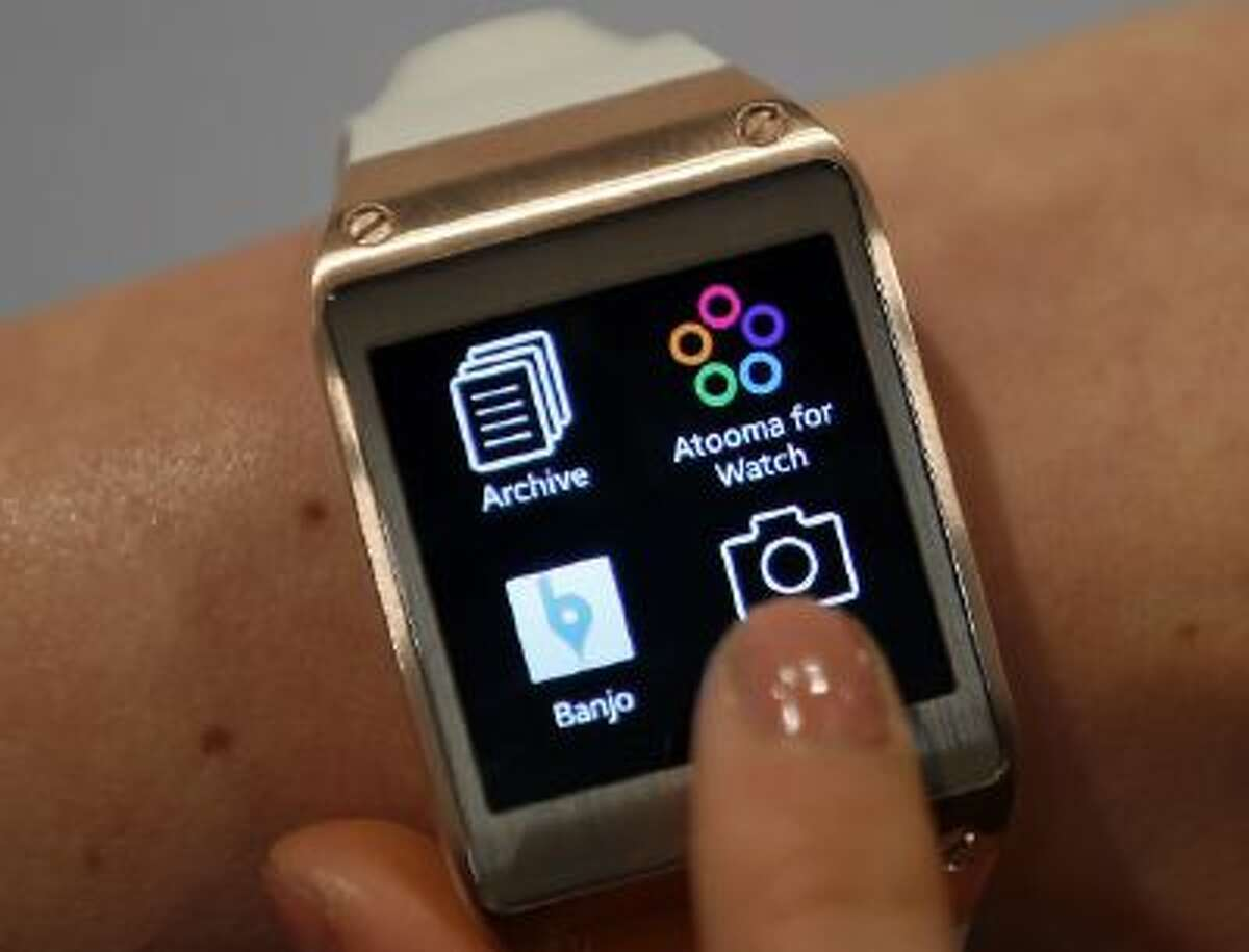 In this Wednesday, Sept. 4, 2013 photo, a model touches the screen of a Samsung Galaxy Gear smartwatch in Berlin, Germany.