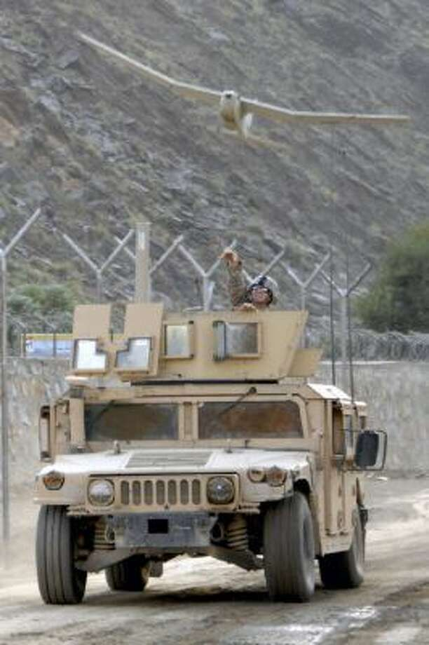 Staff Sergeant Justin McDaniel tosses an Aerovironment Inc. Puma AE unmanned aerial vehicle (UAV) into the air from a moving Humvee during training on the UAV at Forward Operating Base Blessing, Afghanistan, on Oct. 7, 2009. Aerovironment, a maker of small surveillance drones, surprised investors on March 5 by reporting an unprecedented slowdown in military orders.
