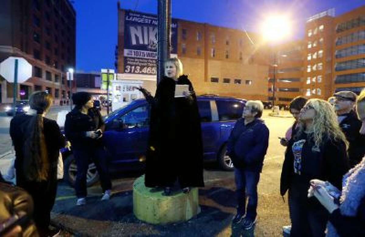 In this Friday, Oct. 18, 2013 photo, Karin Risko, center, tells a ghoulish tale on a Detroit street corner during the