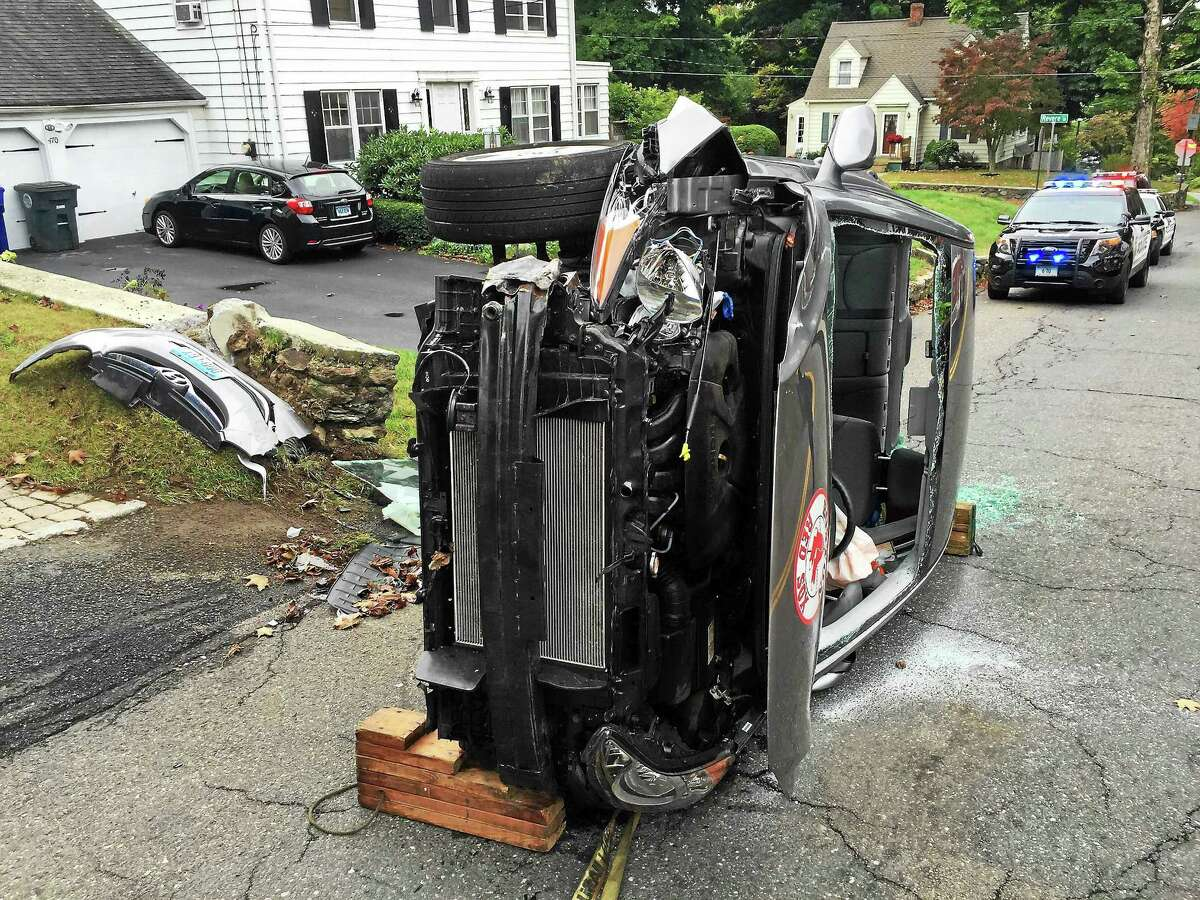 (Ben Lambert - Register Citizen) A woman was rescued after her car flipped over on Charles Street in Torrington early Wednesday afternoon. She suffered minor injuries and the road was closed for a short time.