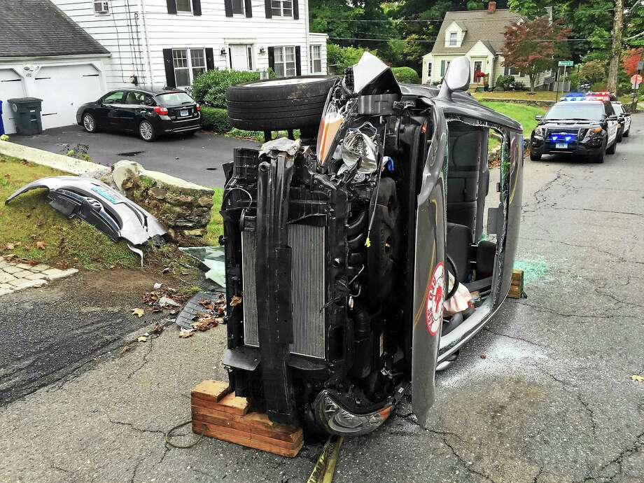 (Ben Lambert - Register Citizen) A woman was rescued after her car flipped over on Charles Street in Torrington early Wednesday afternoon. She suffered minor injuries and the road was closed for a short time. Photo: Journal Register Co.