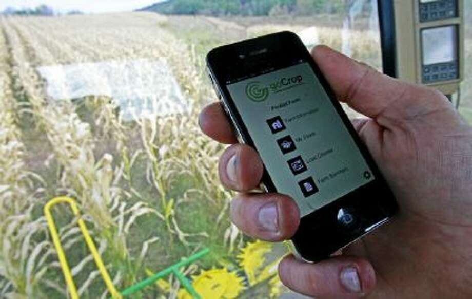 In this Oct. 21, 2013 photo, Tony Pouliot demonstrates the goCrop app on his mobile photo in the cab of his combine on his farm in Westford, Vt.