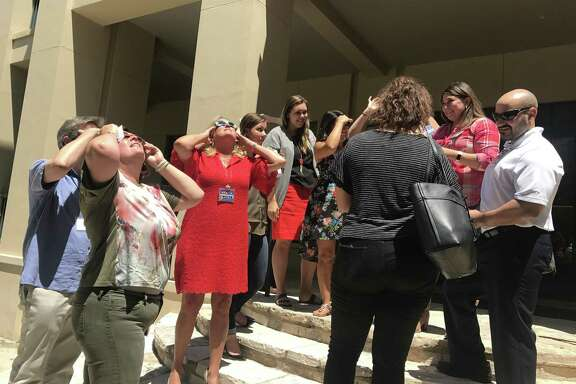 Marketing employees at H-E-B's Arsenal headquarters in downtown San Antonio gaze at the solar eclipse Aug. 21, 2017.
