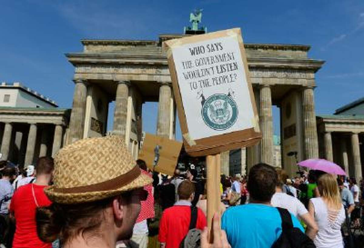 Demonstrators hold up banners as they take part in a protest in front of Berlin's landmark Brandenburg Gate against the US National Security Agency (NSA) collecting German emails, online chats and phone calls and sharing some of it with the country's intelligence services in Berlin on July 27, 2013.