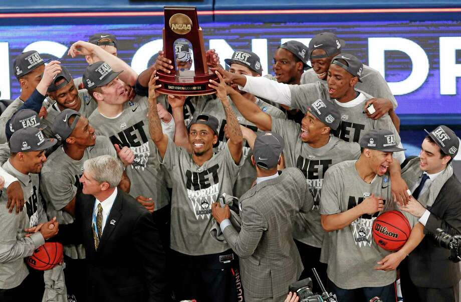 Connecticut players celebrate after defeating Michigan State during a regional final at the NCAA college basketball tournament, Sunday, March 30, 2014, in New York. (AP Photo/Julio Cortez) Photo: AP / AP