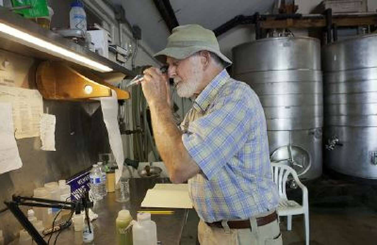 Retzlaff Winery owner Bob Taylor uses a refractometer to check the sugar level of Sauvignon Blanc grapes at Retzlaff Winery in Livermore, Calif., on Thursday, August 15, 2013.